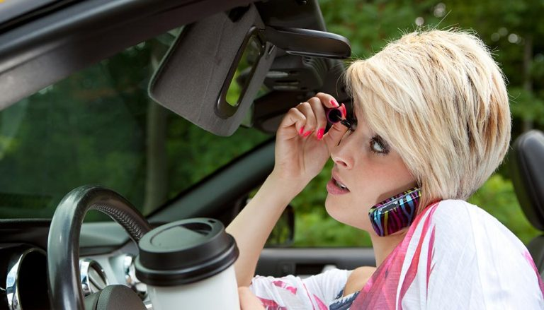 A woman practices bad driving habits