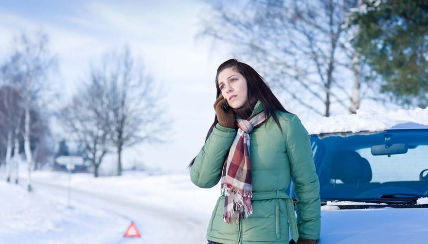 A woman's car in winter is broken down