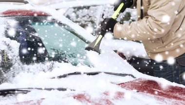 A man uses winter car accessories in the snow