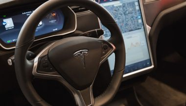 A steering wheel demonstrates the Tesla autopilot feature