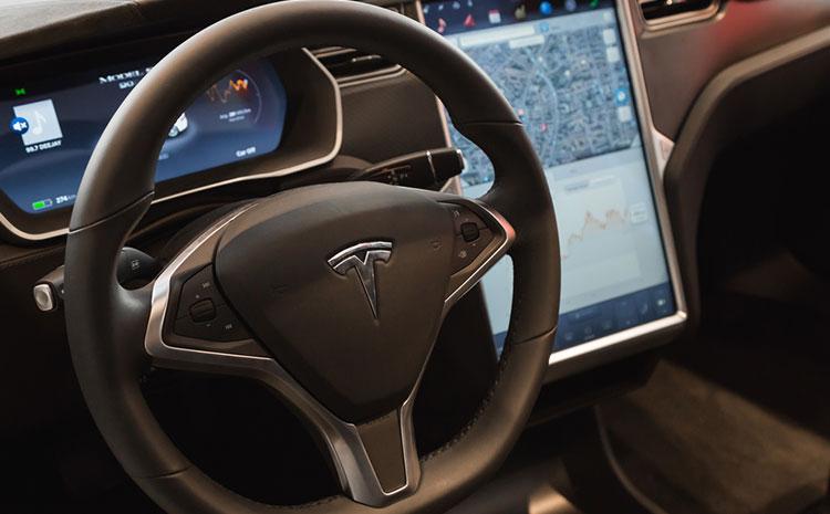 A steering wheel demonstrates the Tesla autopilot feature