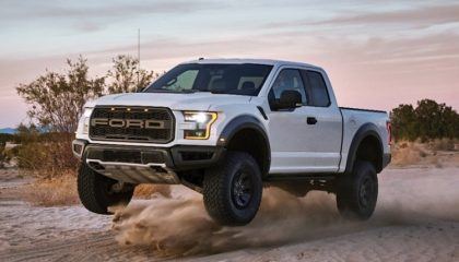 A white Ford Raptor slings some dirt off-roading