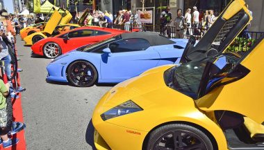 A row of mid-engine supercars lined up at a car show