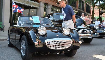 An admirer inspects a tiny Austin Healy Sprite