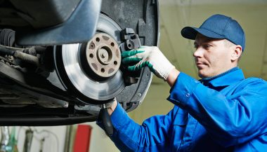 A mechanic begins brake repair work on new disc pads