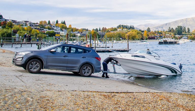 After towing a boat, a car backs the vessel into the water. Don't damage from towing a boat with a car.