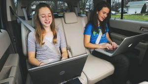 Children use a car's WiFi while on a trip.