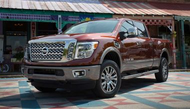 A Nissan Titan XD has large a crew cab, chrome-clad rims, big headlights and a gaping grill.