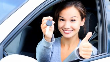 A woman holds the keys to what may be her first used car