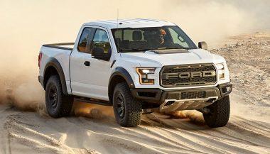 A white Ford F-150 Raptor kicks up some dirt.