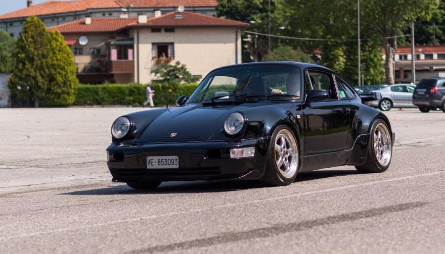 An air-cooled 911 driving down the road.