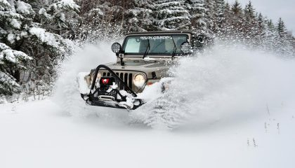 A Jeep Wrangler, one of the best winter SUVs, tackles a snowy road
