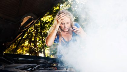 Steam pouring from under a car hood indicates an overheated engine