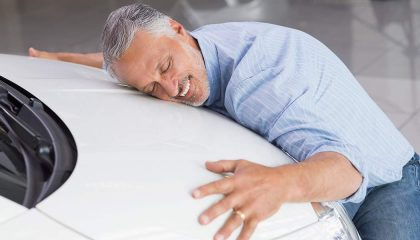 A man hugs his car