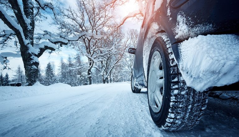 Car driving on snow shows why it is important to winterize your car