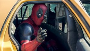 Deadpool getting out of his movei car, a taxi