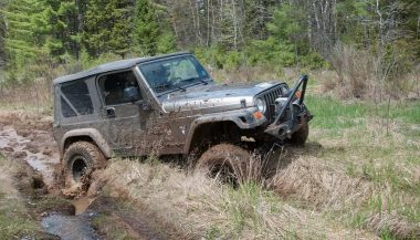 A Jeep Wrangler tearing through a rut shows how it is a dependable off-road vehicle