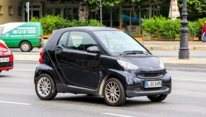 A gas-powered Smart car drives down the street