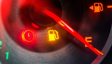 A low fuel light on a dashboard indicates the gas tank is low
