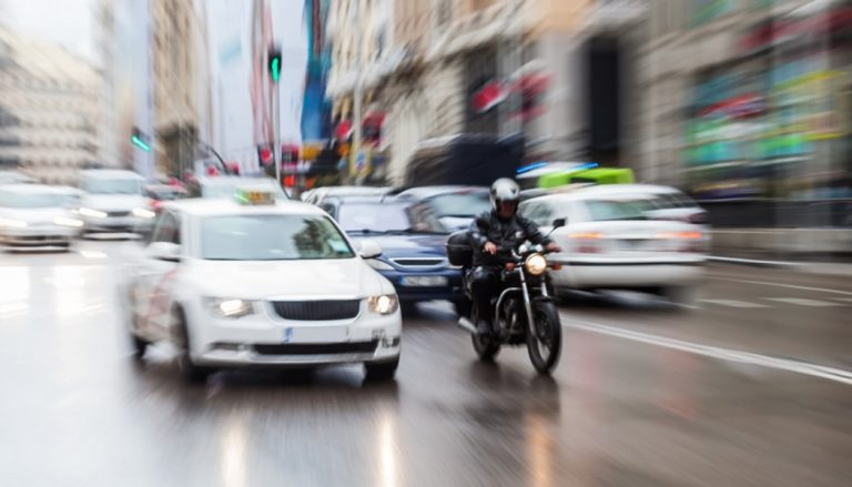A person riding a motorcycle in the rain shows how dangerous the practice can be