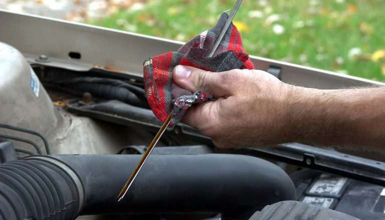 A man checks to see if there is too much oil in car