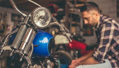 A man doing motorcycle projects in his garage