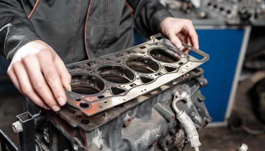 A mechanic fixes a blown head gasket