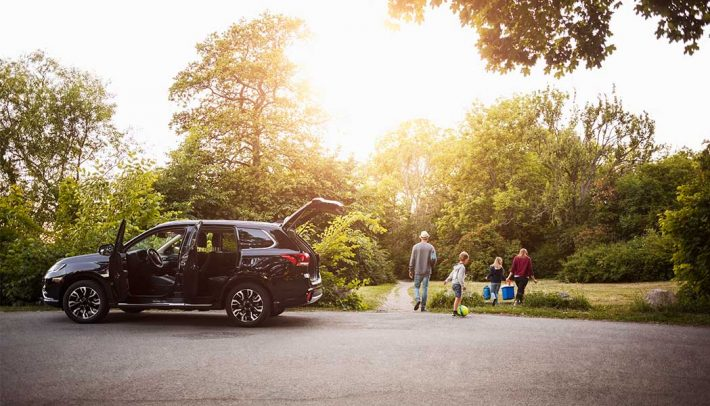 An opened SUV with a family walking near it.